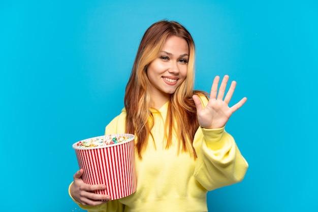 Nastolatek dziewczyna trzyma popcorns na na białym tle niebieskim tle, licząc pięć palcami