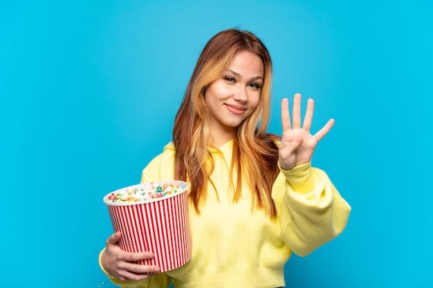 Nastolatek dziewczyna trzyma popcorns na na białym tle niebieskim tle szczęśliwy i liczy cztery palcami