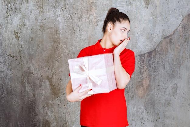 Nastolatek dziewczyna trzyma różowe pudełko owinięte białą wstążką i wygląda miło.