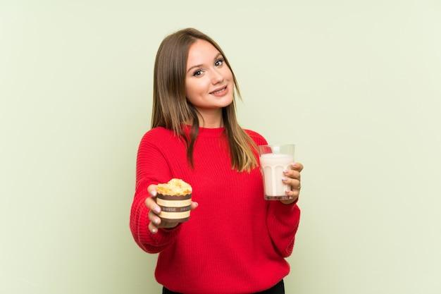 Nastolatek dziewczyna trzyma szklankę mleka i słodka bułeczka
