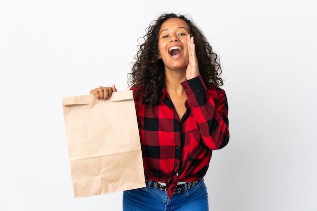 Nastolatek dziewczyna trzyma torbę na zakupy spożywcze na wynos na białym tle na białym tle krzycząc z szeroko otwartymi ustami