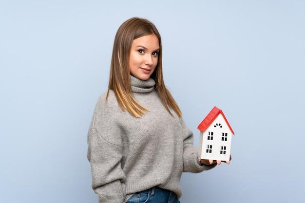 Nastolatek dziewczyna trzyma troszkę dom z pulowerem nad odosobnionym błękitnym tłem