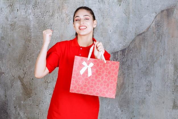 Nastolatek dziewczyna w czerwonej koszuli trzyma czerwoną torbę na zakupy i pokazuje pozytywny znak ręką.
