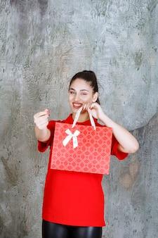 Nastolatek dziewczyna w czerwonej koszuli trzyma czerwoną torbę na zakupy i pokazuje pozytywny znak ręki