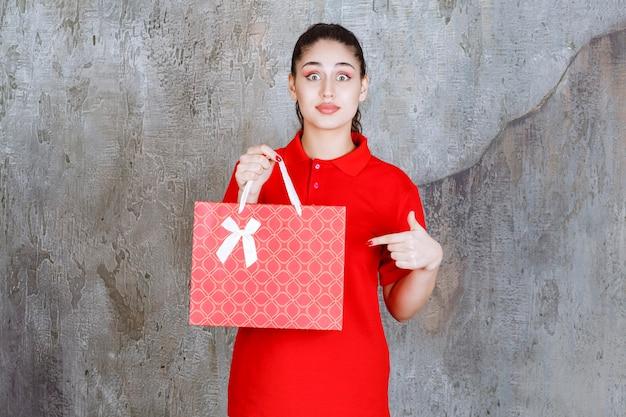 Nastolatek dziewczyna w czerwonej koszuli trzyma czerwoną torbę na zakupy i wygląda przestraszony i przerażony.