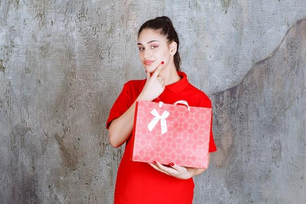 Nastolatek dziewczyna w czerwonej koszuli trzyma czerwoną torbę na zakupy i wygląda zdezorientowany i zamyślony.