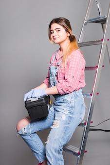 Nastolatek dziewczyna w ogólnym na drabinie z narzędziowym pudełkiem