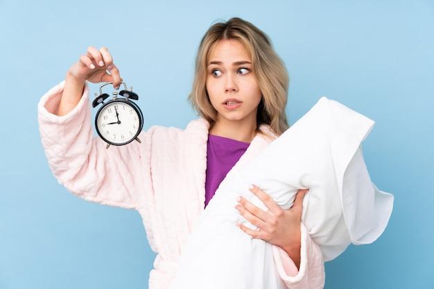 Nastolatek dziewczyna w piżamie na błękit ścianie