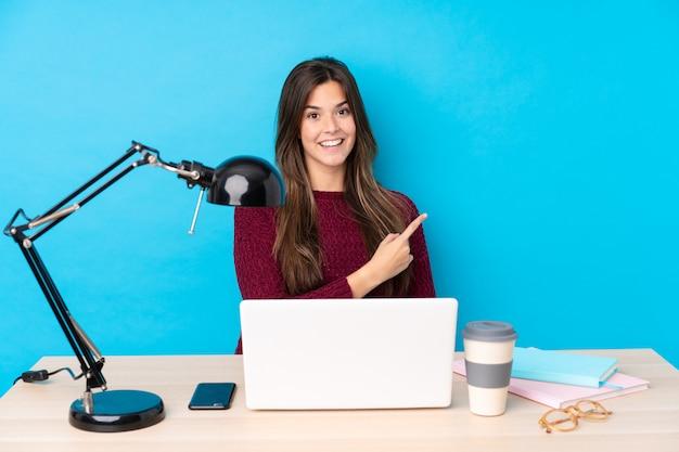 Nastolatek dziewczyna w stole z jej komputerem osobistym