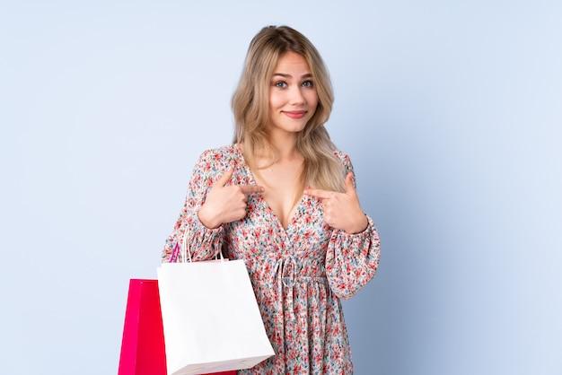 Nastolatek dziewczyna wskazuje na ona z torba na zakupy na błękit ścianie
