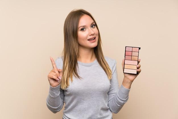 Nastolatek dziewczyna wskazuje w górę doskonałego pomysłu z makeup paletą nad odosobnionym tłem