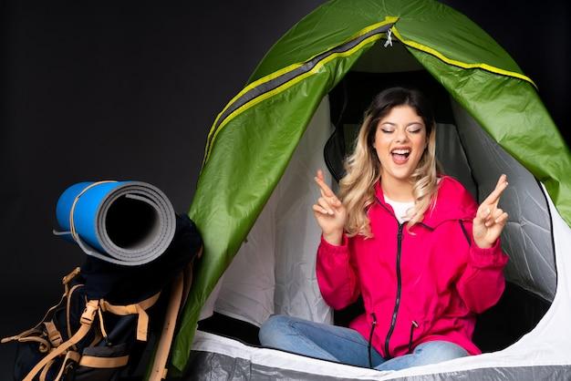 Nastolatek dziewczyna wśrodku campingowego zielonego namiotu na czerni ścianie z palców krzyżować