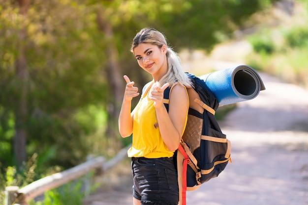 Nastolatek dziewczyna wycieczkuje przy outdoors wskazywać ono uśmiecha się i przód