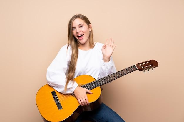 Nastolatek dziewczyna z gitarą salutuje z ręką z szczęśliwym wyrażeniem