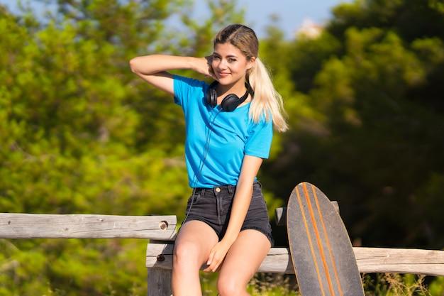 Nastolatek dziewczyna z łyżwą przy outdoors robi telefonu gestowi. zadzwoń do mnie znak