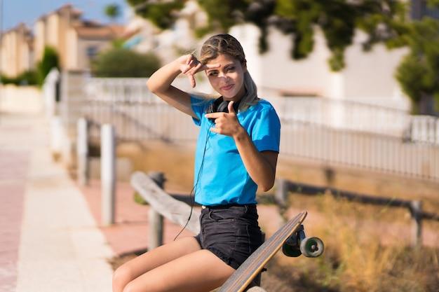 Nastolatek dziewczyna z łyżwą przy outdoors skupia się twarz. symbol kadrowania