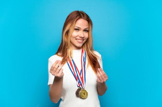 Nastolatek dziewczyna z medalami na odizolowanej ścianie robi pieniądze gestowi