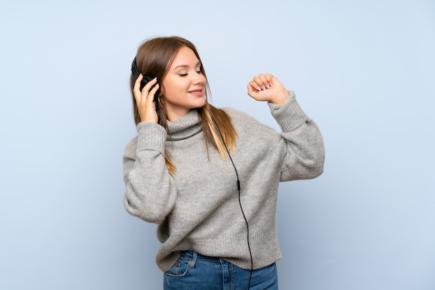 Nastolatek dziewczyna z pulowerem nad odosobnioną błękit ścianą słucha muzyka z hełmofonami