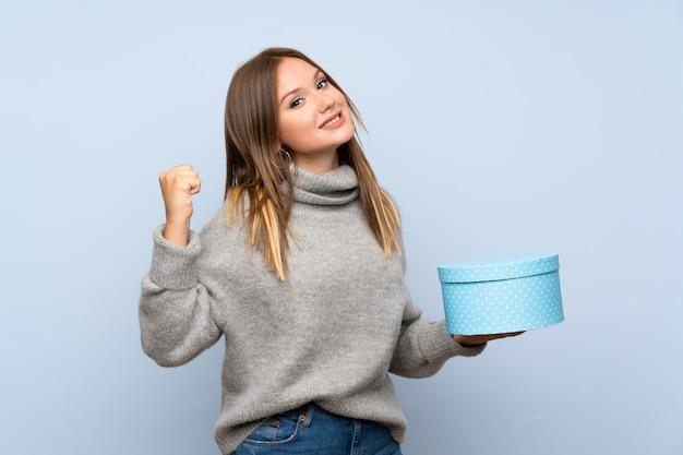 Nastolatek dziewczyna z pulowerem nad odosobnionym błękitnym tła mienia prezenta pudełkiem