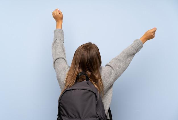 Nastolatek dziewczyna z pulowerem odizolowywającym nad z plecakiem