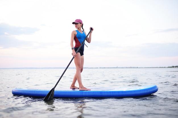 Nastolatek dziewczyna z sup deską na morzu. aktywność surfowania wiosła