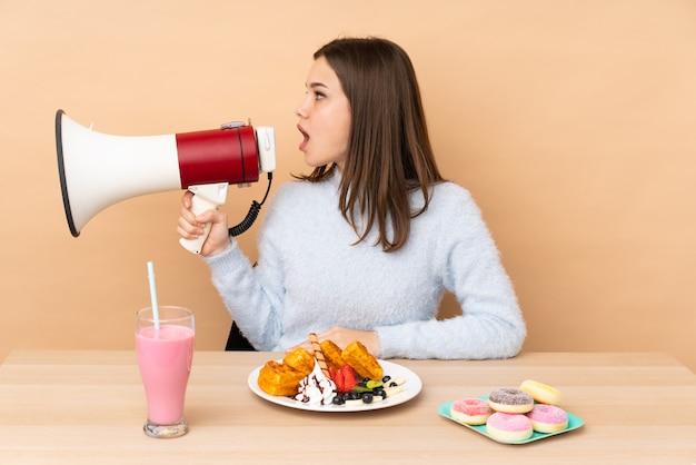 Nastolatek dziewczyny jedzenia gofry na beżowej ścianie krzyczy przez megafon