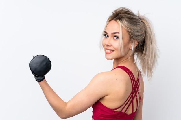 Nastolatek dziewczyny mienia gofry nad odosobnioną błękit ścianą robi weightlifting