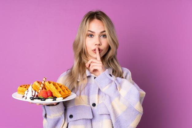 Nastolatek dziewczyny mienia gofry odizolowywający na purpurach izolują pokazywać znak cisza gesta kładzenia palec w usta