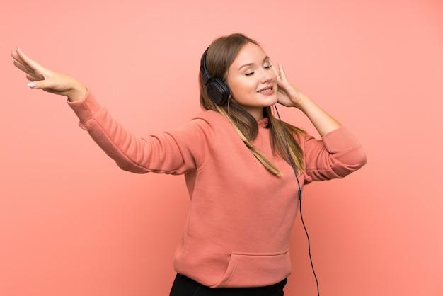 Nastolatek dziewczyny słuchająca muzyka i taniec nad odosobnioną menchii ścianą