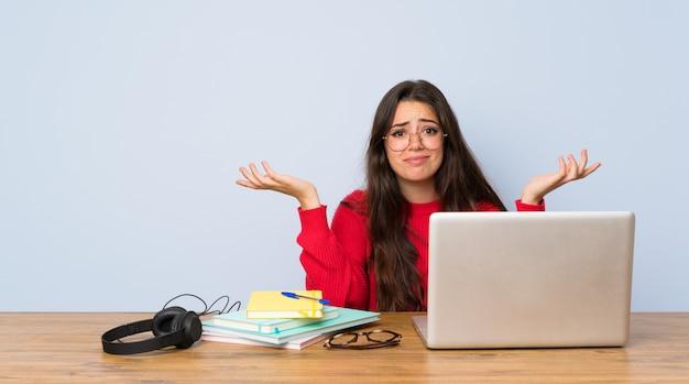 Nastolatek dziewczyny studencki studiowanie w stole ma wątpliwości podczas gdy podnoszący rękę
