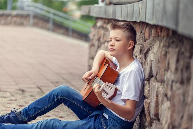 Nastolatek gitara akustyczna bawić się siedzieć na krokach w parku.