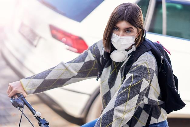 Nastolatek jadący do szkoły rowerem i noszący maskę na twarz z powodu pandemii koronawirusa
