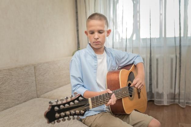 Nastolatek jest w domu i sam gra na gitarze.