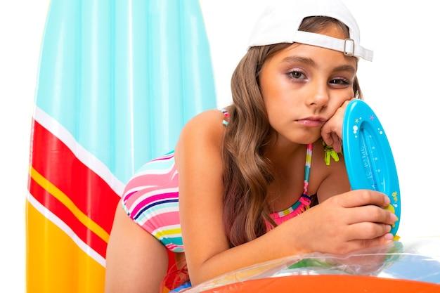 Nastolatek kaukaski dziewczyna w czerwone okulary przeciwsłoneczne, strój kąpielowy, biała czapka z gumowymi materacami na białym tle