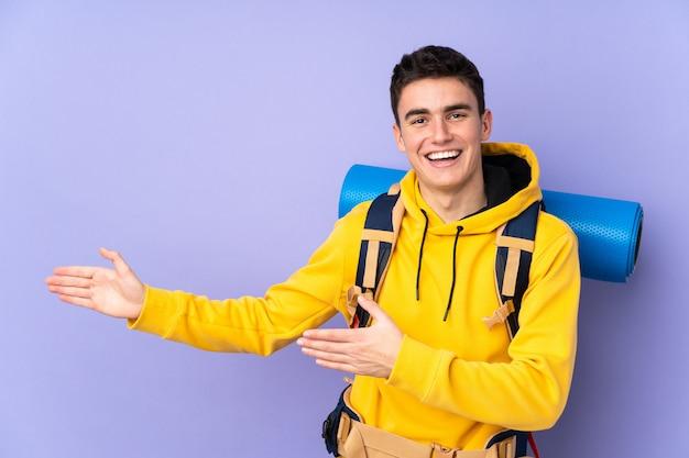 Nastolatek kaukaski góral mężczyzna z dużym plecakiem na białym tle na fioletowym tle wyciągając ręce na bok do zapraszania