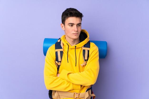 Nastolatek kaukaski góral mężczyzna z wielkim plecakiem na fioletowym ścianie myślenia pomysł