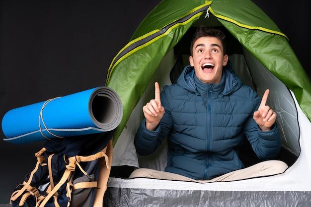 Nastolatek kaukaski mężczyzna w środku camping zielony namiot na czarnej ścianie zaskoczony i skierowany w górę