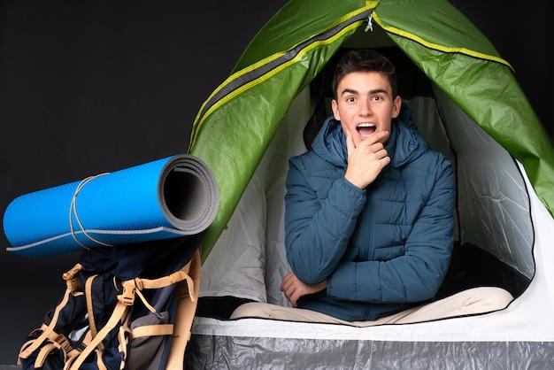 Nastolatek kaukaski mężczyzna w środku camping zielony namiot na czarnym tle zaskoczony i zszokowany, patrząc w prawo