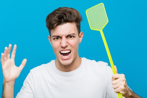 Nastolatek kaukaski mężczyzna za pomocą flyswatter