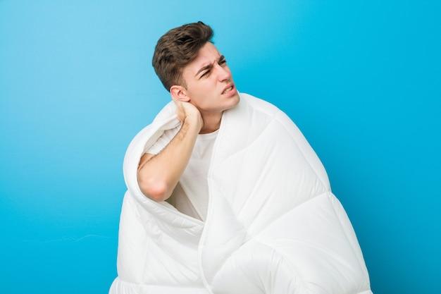 Nastolatek kaukaski zmęczony człowiek obejmujący się kocem