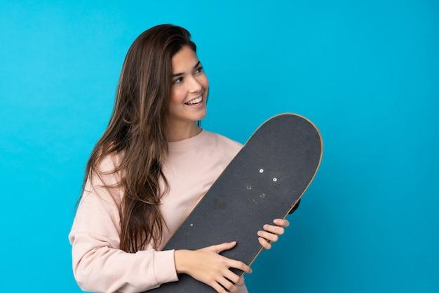 Nastolatek kobieta nad odosobnioną błękit ścianą z łyżwą z szczęśliwym wyrażeniem
