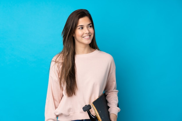 Nastolatek kobieta nad odosobnioną błękit ścianą z łyżwą