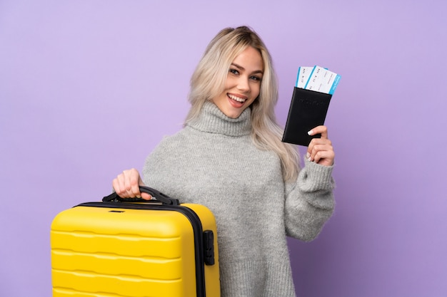 Nastolatek kobieta nad odosobnioną purpury ścianą w wakacje z walizką i paszportem