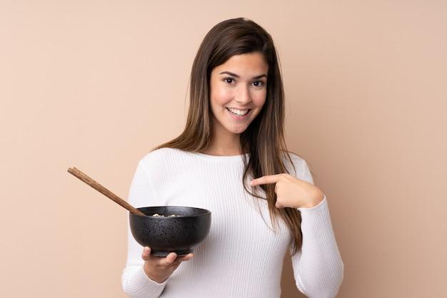 Nastolatek kobieta nad odosobnioną ścianą z niespodzianka wyrazem twarzy podczas gdy trzymający puchar kluski z chopsticks