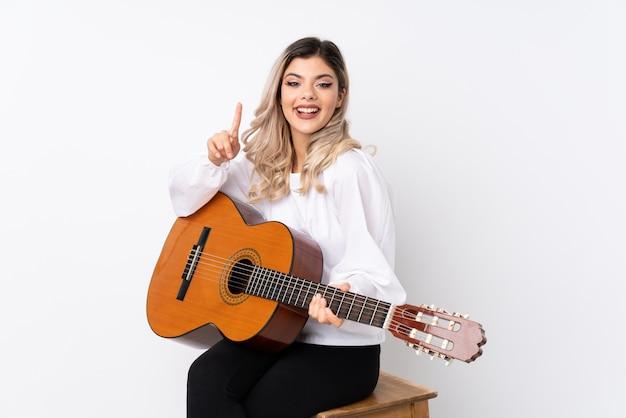 Nastolatek kobieta z gitarą nad odosobnionym bielem wskazuje w górę doskonałego pomysłu