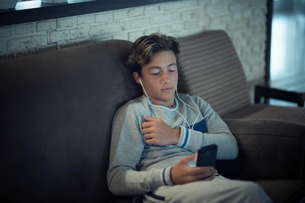 Nastolatek leżał samotnie na kanapie w domu, używając telefonu i słuchając muzyki - oglądając filmy lub surfując po internecie w nocy - media społecznościowe i uzależniony od sieci styl życia i koncepcja