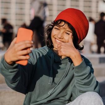 Nastolatek na zewnątrz biorąc selfie, jednocześnie dając kciuki do góry