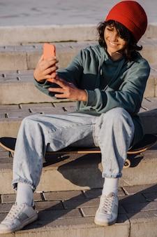 Nastolatek na zewnątrz siedzi na deskorolce i biorąc selfie