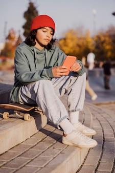 Nastolatek na zewnątrz siedzi na deskorolce i trzymając smartfon