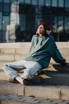 Nastolatek na zewnątrz słucha muzyki na słuchawkach, siedząc na deskorolce